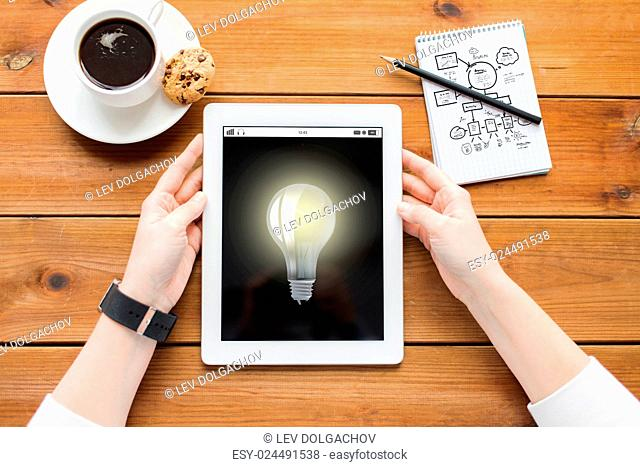 business, idea, technology and people concept - close up of woman with light bulb on tablet pc computer screen, notebook and coffee on wooden table