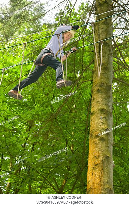 A women on the the Go Ape aerial challenge in Grizedale Forest in Cumbria UK
