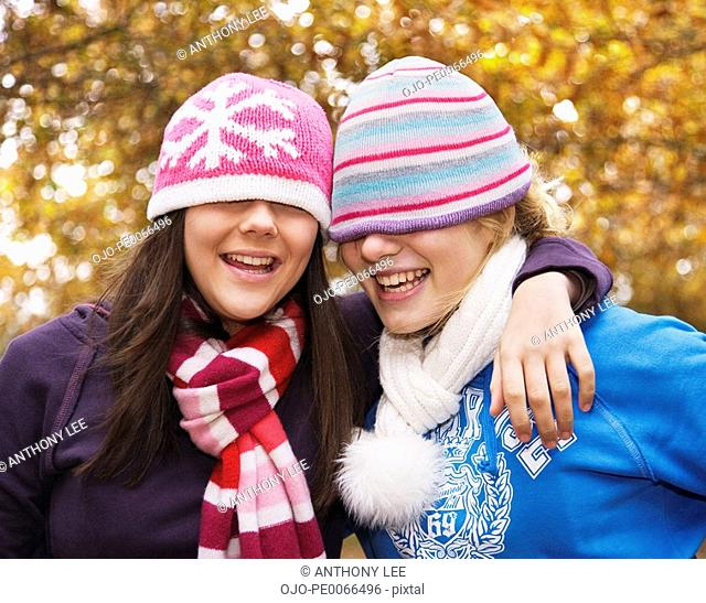 Girls in scarves and caps hugging outdoors