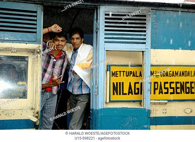 Loughing young indian men on board the Nilgiri Mountain Railway at Coonoor railway station in rain. India, Tamil Nadu, Coonoor 2005