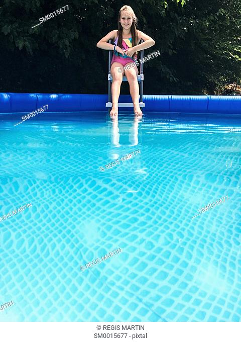 Girl sitting on the edge of a swimming pool and looking at the camera