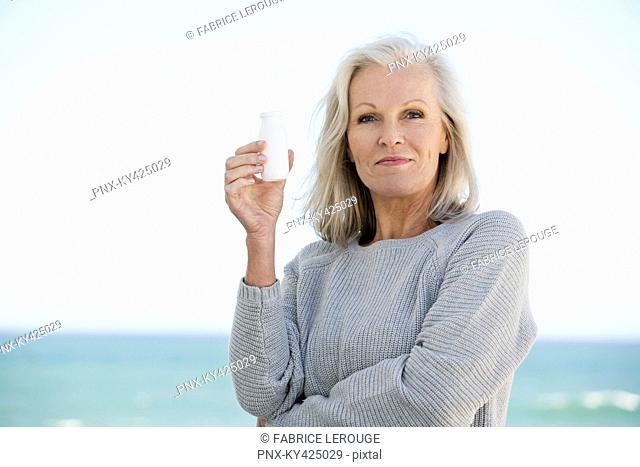 Woman holding a bottle of probiotic drink