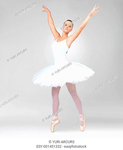 Full length of a young ballerina wearing white tutu dancing against white background