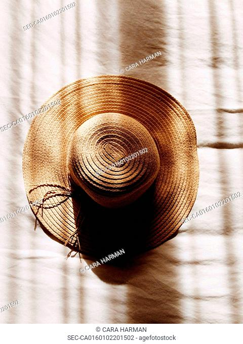 Sunhat on white in shadow stripes