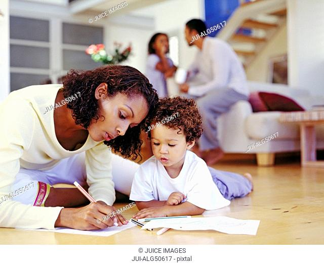 African american mother and son drawing on floor
