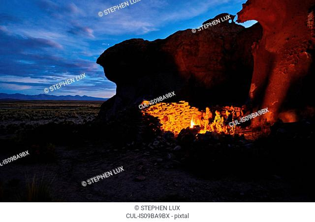 Mother and sons, sitting beside camp fire at dusk, Oruro, Oruro, Bolivia, South America