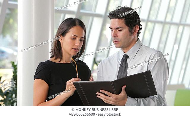 Camera tracks businesswoman and businessman in modern office discussing report together.Shot on Canon 5d Mk2 with a frame rate of 30fps