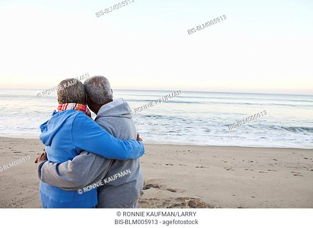 African American couple hugging on beach