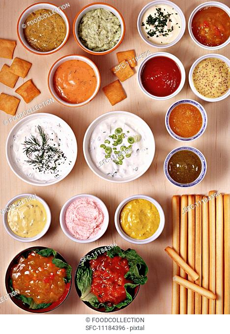Lots of different dips in bowls with crackers and grissini