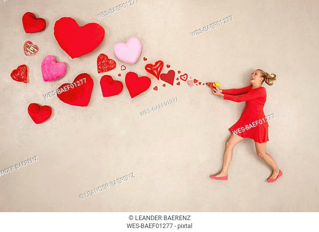 Young woman shooting hearts with a pistol