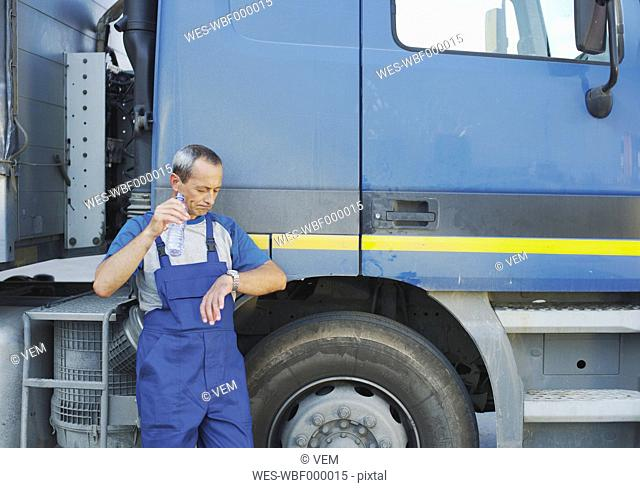 Italy, Chiajna, Truck-Driver standing by truck