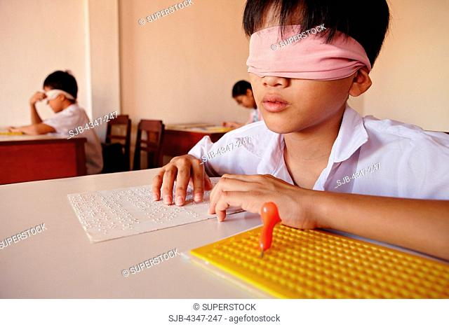 A Vietnamese boy with damaged eyesight is learning the Braille alphabet in the blind school in Vietnam. His eyes are covered with a scarf