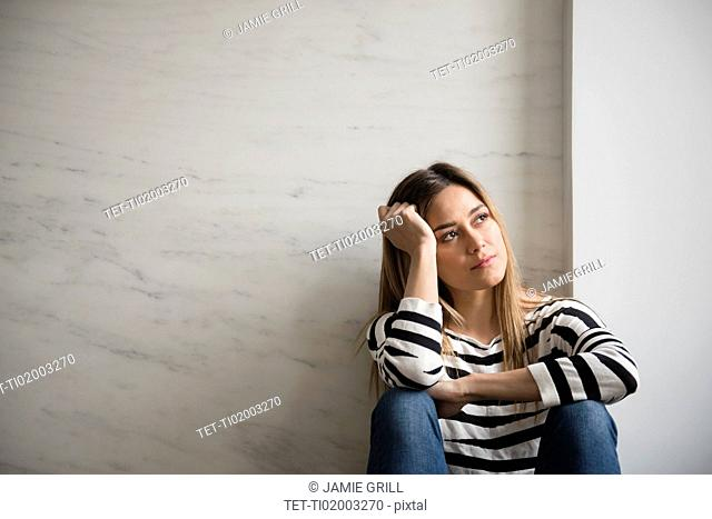 Young woman wearing striped top daydreaming