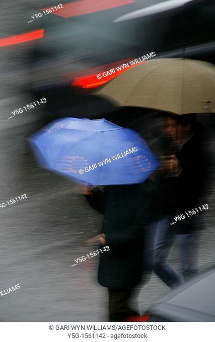 person with umbrella crossing road in rain