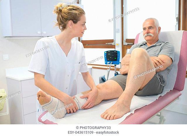 nurse bandaging leg of senior patient in hospital