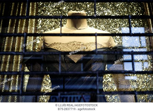 Bust of a mannequin in an elegant dress in the shop window with reflections on the glass and seen through a metal grate. Soho, City of Westminster, West End