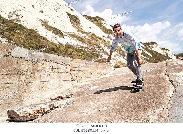Young male skateboarder skateboarding down cliff sea wall