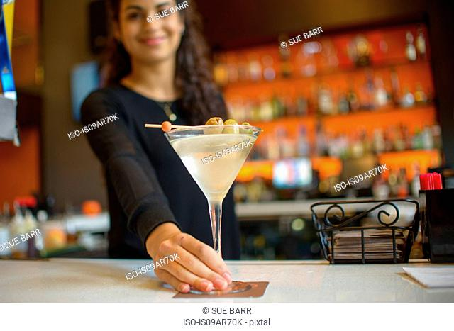 Young female bartender handing cocktail on counter of cocktail bar