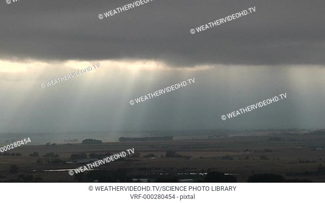 Timelapse footage of sunbeams, or crepuscular rays, shining through broken cloud. High moisture levels in the air make the sunbeams visible