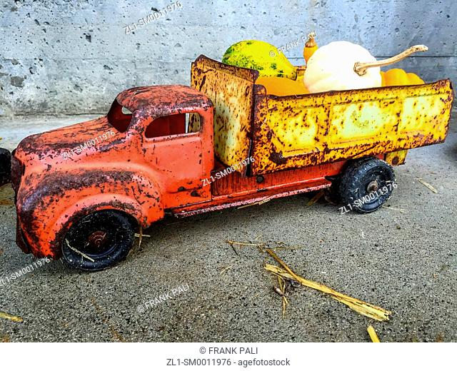 Rusty old toy truck with a load of small pumpkins