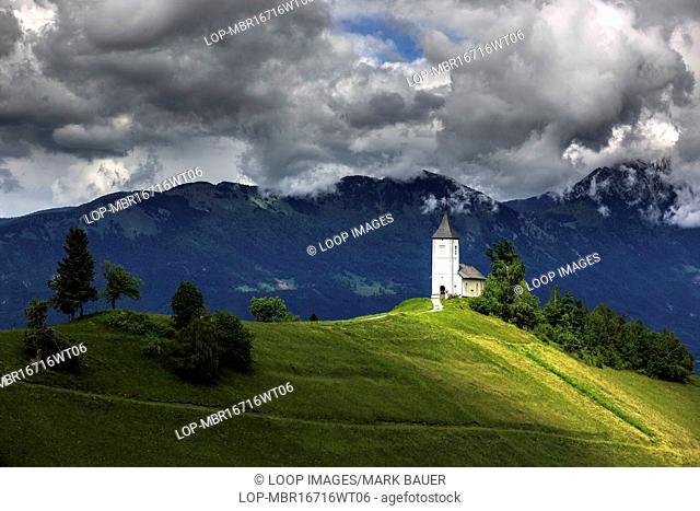 Stormy sky above St Primoz church near Jamnik in Slovenia