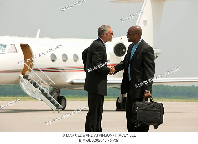 Businessmen shaking hands on airport tarmac
