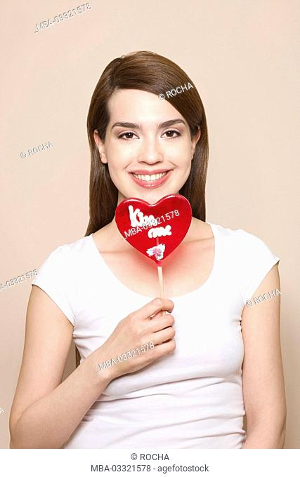 Woman holds heart-shaped lollipop in her hand, happy, smile, portrait