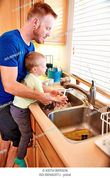 Father washing son's hands in kitchen sink
