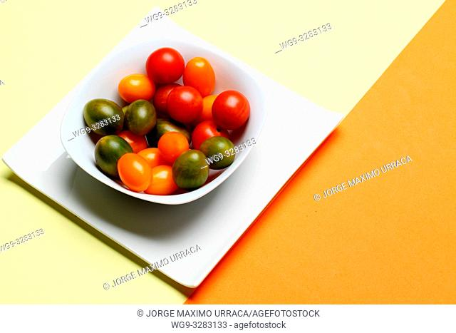 Small tomatoes with different colors in white bowl on light yellow and orange background