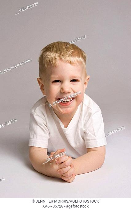 Blond haired, blue-eyed 3-yera-old boy lying on his stomach, hands clasped and smiling at the camera, wearing white t-shirt