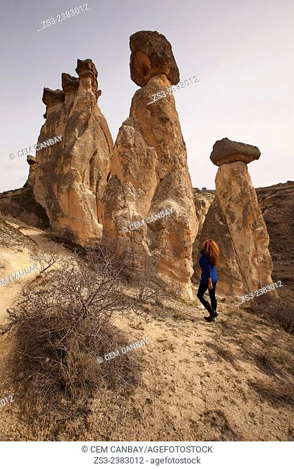 Woman near the fairy chimneys in Cavusin, Cappadocia Region, Nevsehir, Central Anatolia,Turkey, Europe