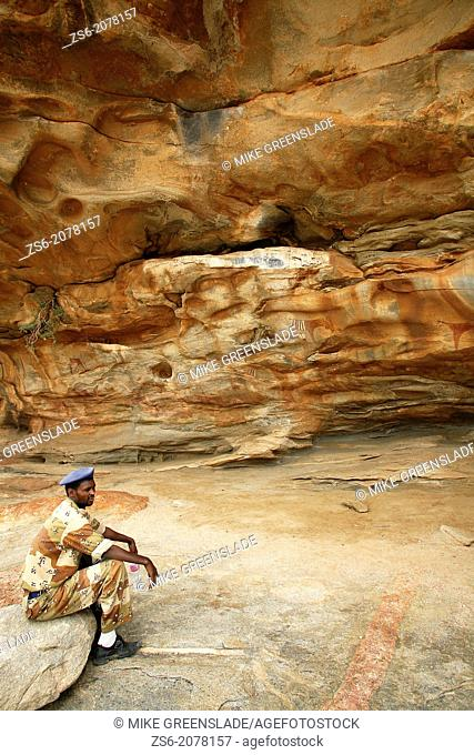 Uniformed guard outside neolithic cave paintings, Laas Geel, Naasa Hablood Hills, Somaliland, Somalia