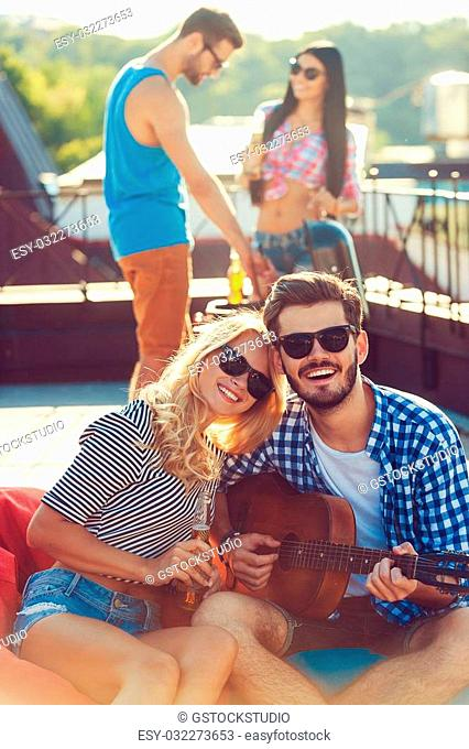 Enjoying time with friends. Beautiful young couple bonding to each other and sitting on the bean bag with guitar while two people barbecuing in the background