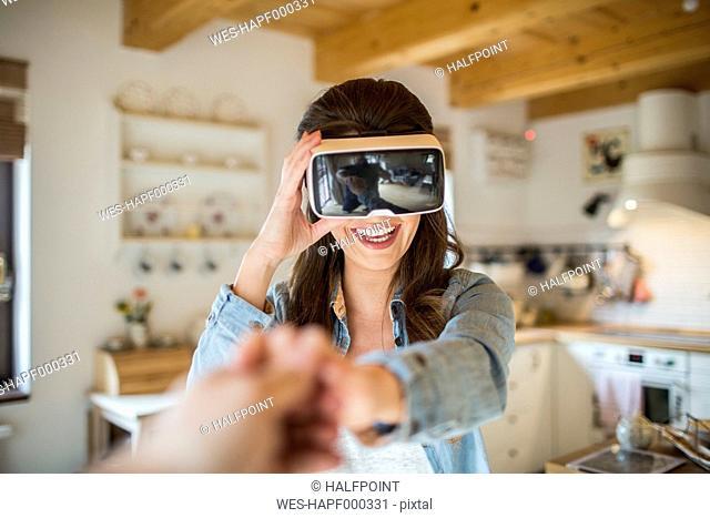 Young woman at home using Virtual Reality goggles