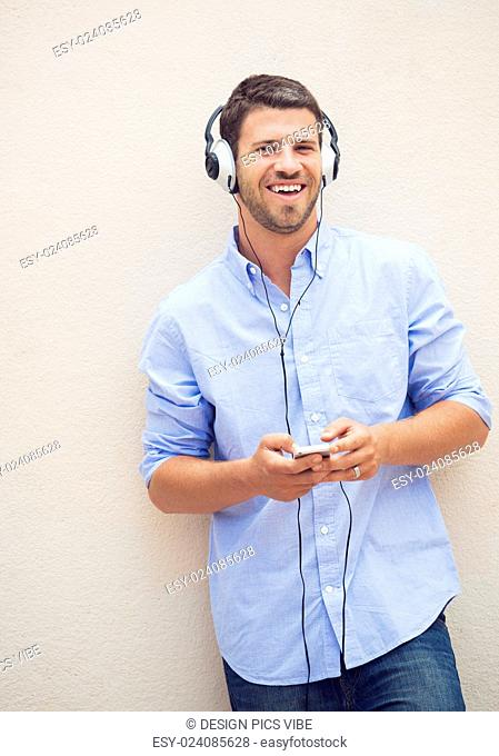 Happy young man listening to music with headphones
