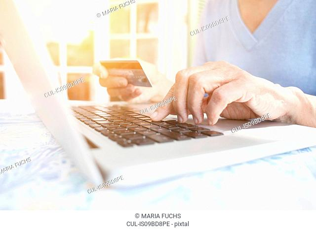 Cropped view of woman holding credit card using laptop
