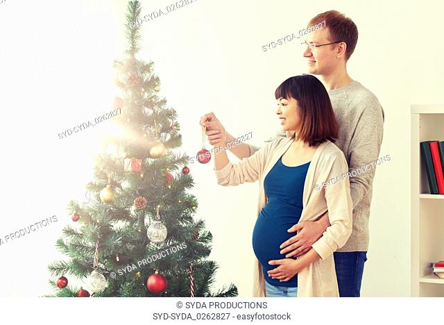 happy pregnant wife and husband at christmas tree