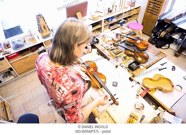 Violin maker making violins in production studio