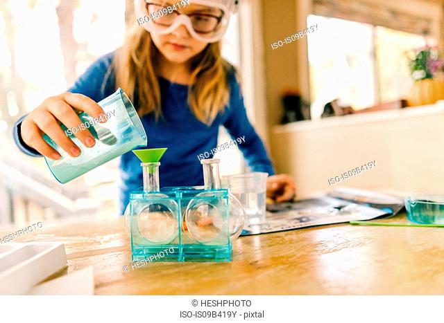 Girl doing science experiment, pouring liquid into flask