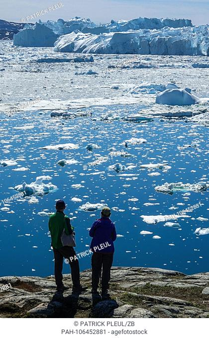 20.06.2018, Gronland, Denmark: Two tourists stand on the shore in front of large icebergs in the coastal town of Ilulissat in western Greenland