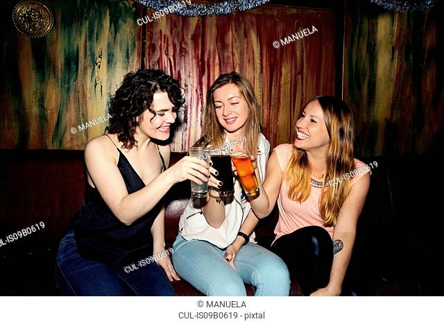 Three adult female friends raising a glass in bar