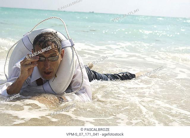 Mature man with a life belt in water