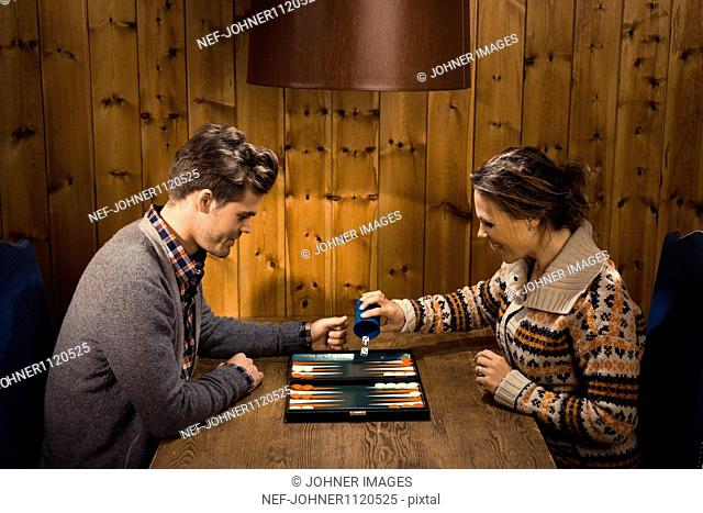 Man and woman playing backgammon, smiling