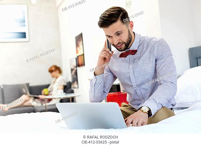 Man in bow tie talking on cell phone and using laptop on bed