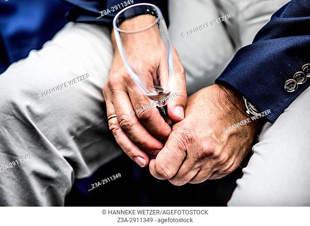 Close-up of male hands with empty champagne flute