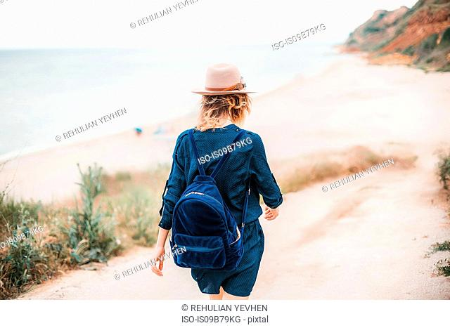 Mid adult woman walking towards beach, rear view