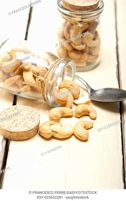 cashew nuts on a glass jar over white rustic wood table