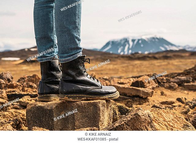 Iceland, woman standing on volcanic rock