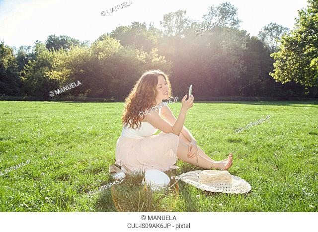 Young woman sitting on park grass looking at smartphone