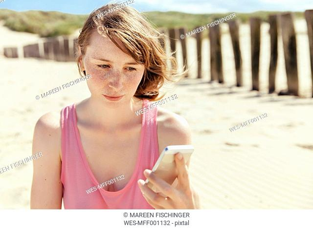 Woman looking at her smartphone on the beach